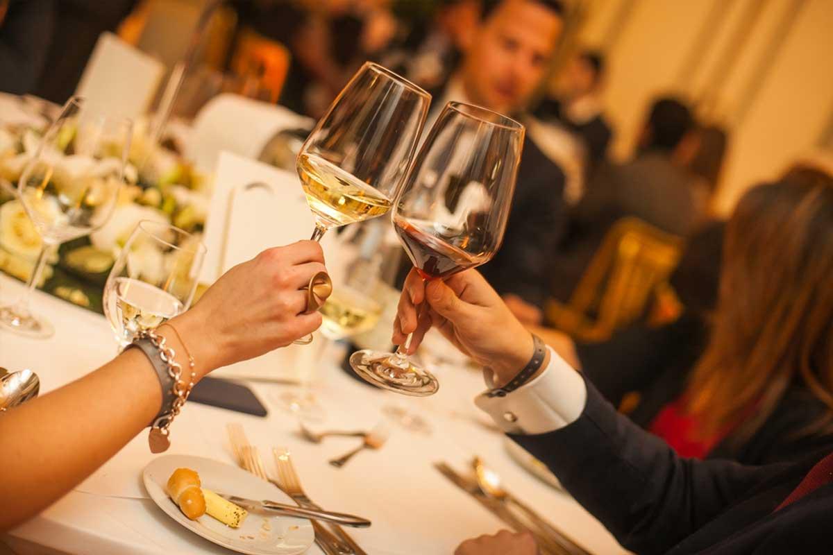 Dinner & Konzert Wien - Nahaufnahme beim Dinner von zwei Weingläsern die anstoßen